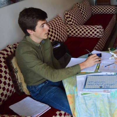 Projects Abroad volunteer goes through his Arabic homework given to him during the language lessons.